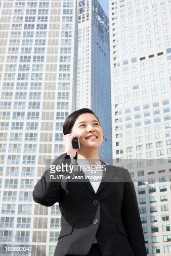 Felice giovane donna in carriera al telefono davanti : Foto stock