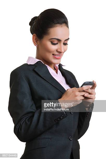 Happy young businesswoman using mobile phone isolated over white background