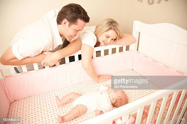 Happy Young Caucasian Couple adoring their baby in her crib