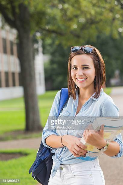 Happy young college student walking on beautiful campus