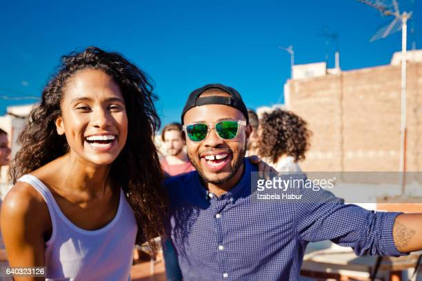 Happy young couple at rooftop party