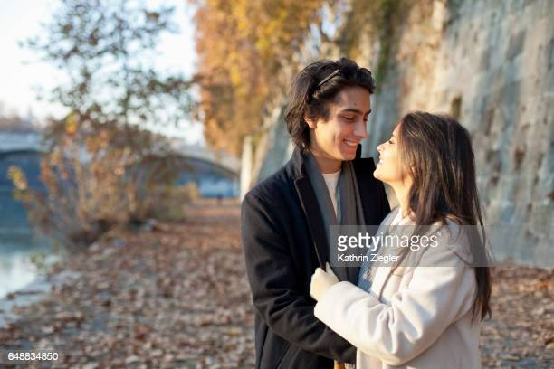 Happy young couple at the riverbank of the Tiber river, Rome, Italy