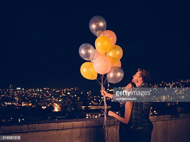 Glückliches junges Paar feiert mit bunten Ballons auf dem Dach