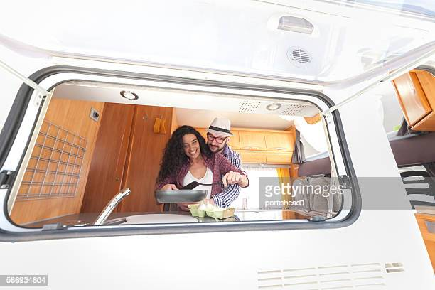 Happy young couple cooking together inside of a camper