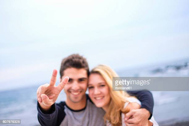 Happy young couple embracing and making victory sign