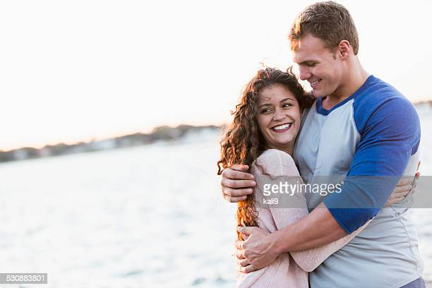 Happy young couple embracing by the water