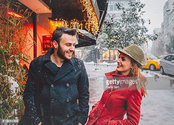 Happy young couple enjoying outdoor in snowy winter time