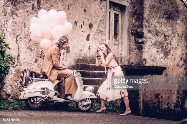 Glada unga par njuter av Photoshoting på Vintage Vespa