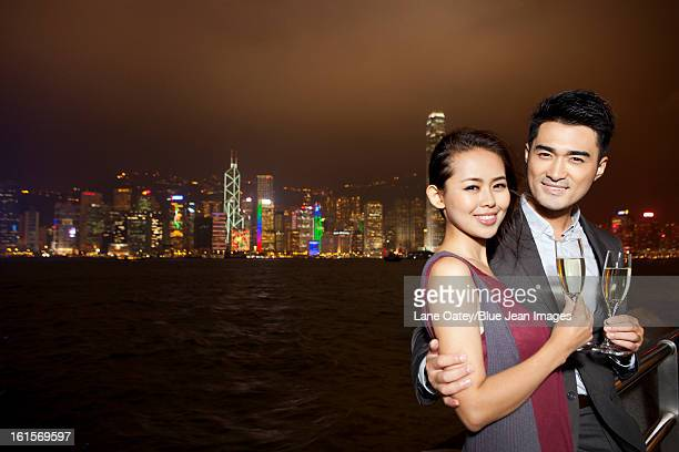 Happy young couple enjoying the night view of Victoria Harbor with champagne, Hong Kong