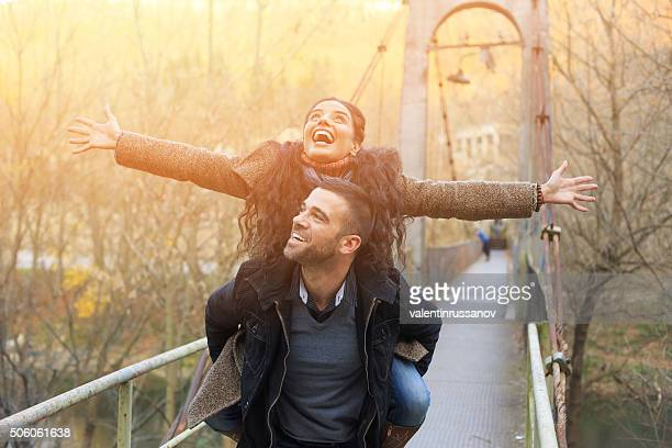 Happy young couple flying on bridge