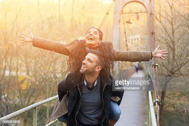 Glückliches junges Paar fliegen auf Brücke