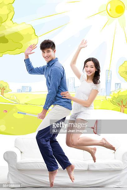Happy young couple flying on broom
