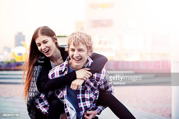 幸せな若いカップルの楽しいピギーバック、東京。