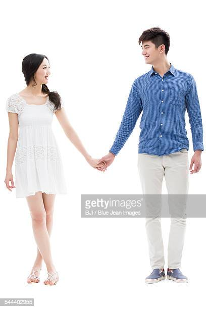 Happy young couple holding hands