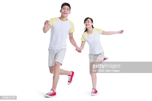 Happy young couple holding hands running
