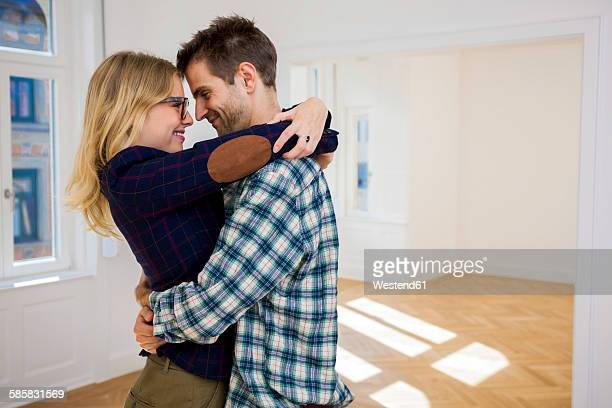 Happy young couple hugging in empty apartment