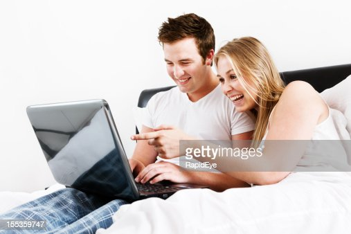 Happy young couple in bed smile at laptop screen