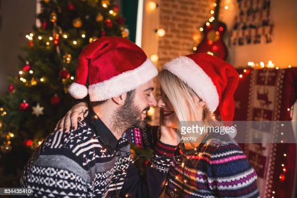 Happy Young Couple in love sitting by the Christmas tree, Happy New Year