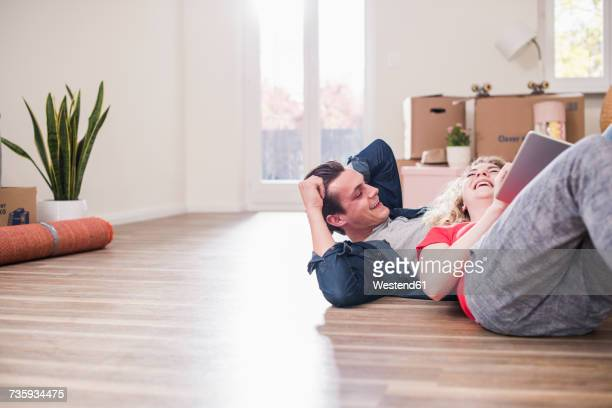 Happy young couple in new home lying on floor with tablet