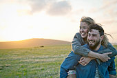 Happy young couple in rural field, Dorset, England