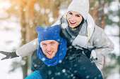 Happy Young Couple in Winter Park having fun.Family Outdoors