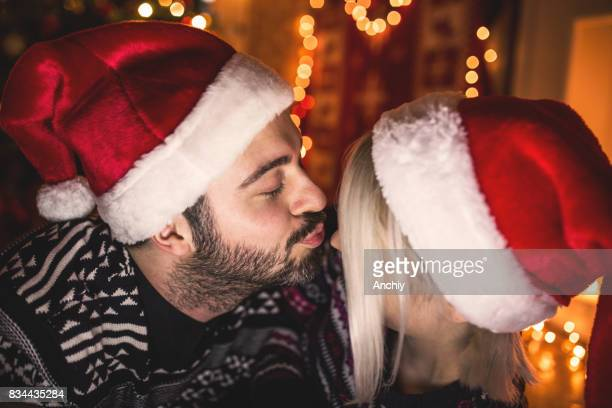 Happy Young Couple is kissing by the Christmas tree, Happy New Year