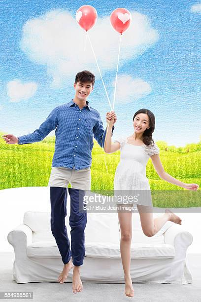 Happy young couple jumping with balloon