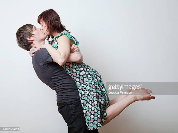 Happy young couple kissing in studio