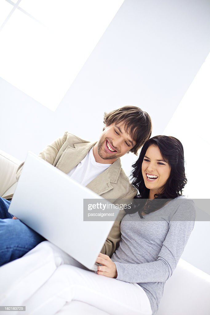Happy young couple laughing while using a laptop : Stock Photo