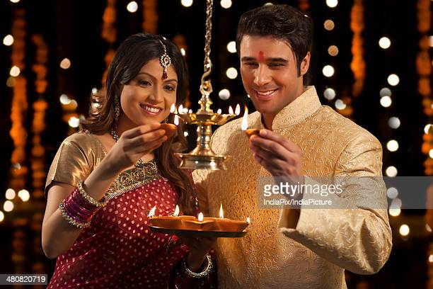 Happy young couple lighting up the oil lamps during Diwali