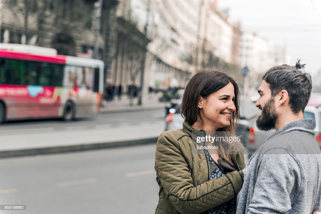 Happy young couple looking at each other on the street : Bildbanksbilder