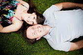 Happy Young Couple Lying Down Outside In Grass