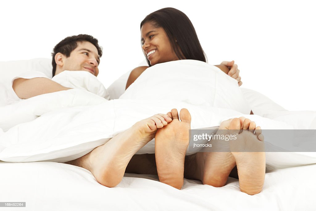 Happy Young Couple Lying in Bed Playing Footsie : Stock Photo