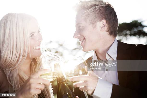 Happy young couple outdoors drinking wine