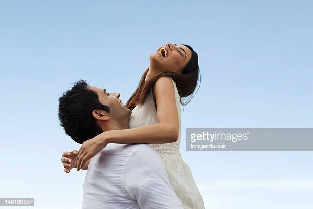 Happy young couple playing against blue sky