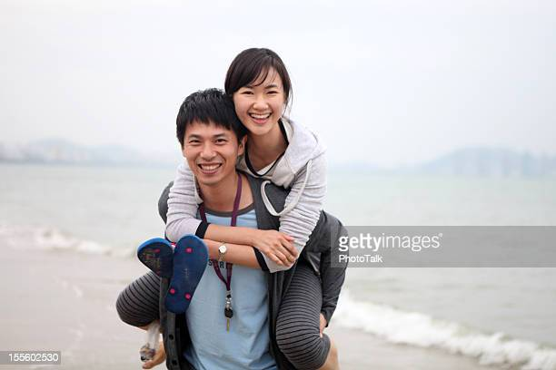 Happy Young Couple Playing On Beach - XLarge