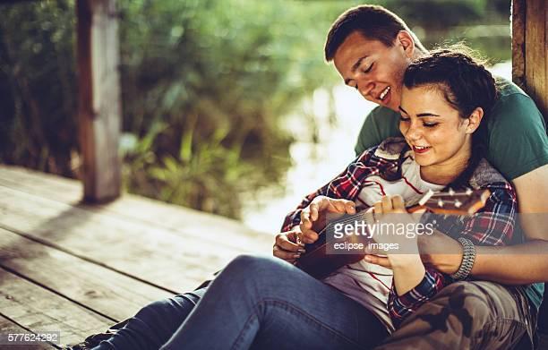 Happy young couple playing ukelele