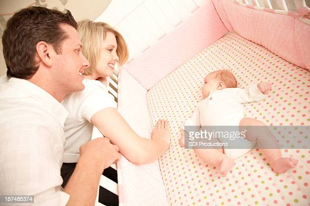 Happy Young Couple playing with their little baby in crib