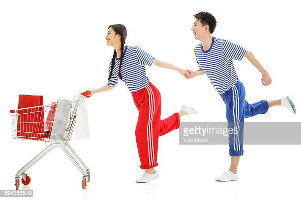 Happy young couple push a shopping cart