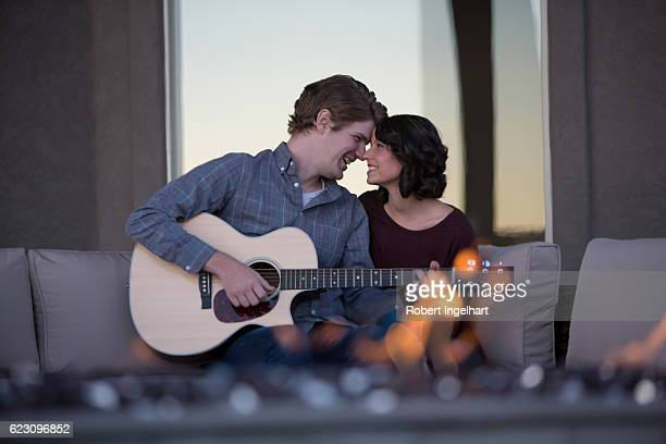 Happy Young Couple Relaxing in Back Yard with Firepit