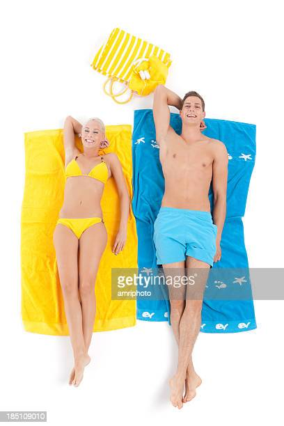 happy young couple relaxing on beach towels
