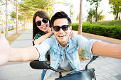 happy young couple riding  scooter and making selfie photo