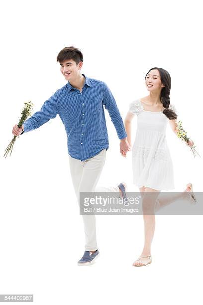Happy young couple running with flowers