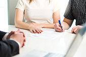 Happy young couple signing agreement or contract. Health insurance document, bank loan, mortgage or apartment rental paper. Woman and man having meeting with salesman or real estate agent.