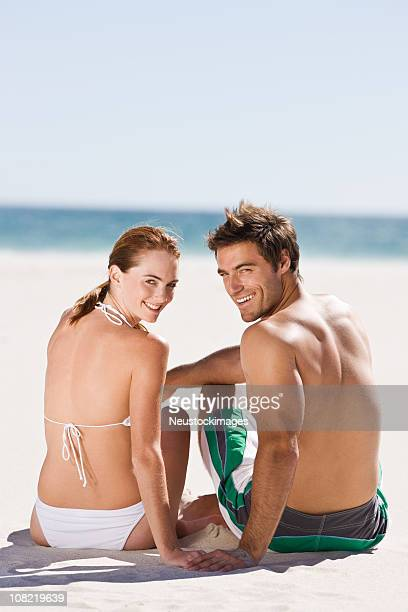 Happy young couple sitting at beach