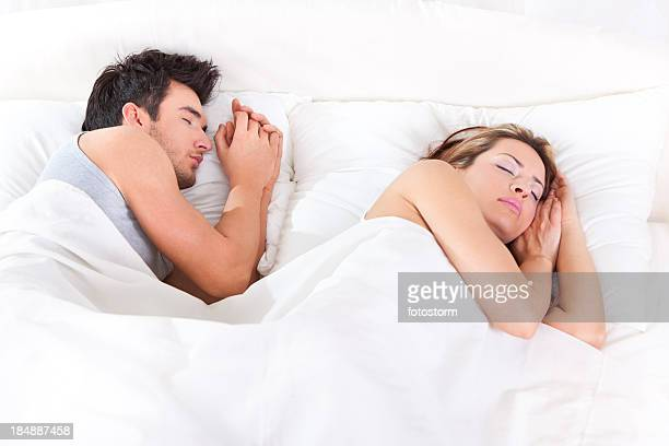 Happy young couple sleeping in the bed