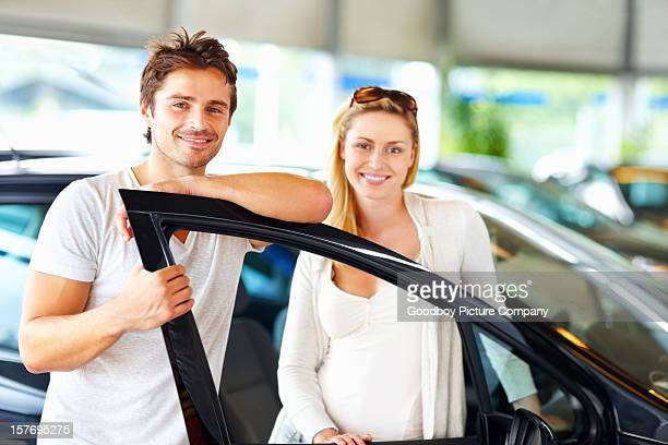 Happy, young couple standing by new car in showroom
