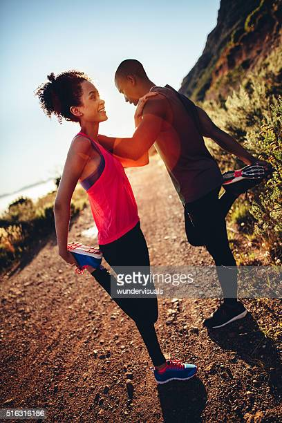 Happy young couple supporting together and doing stretching for running