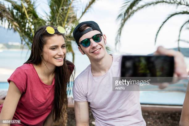 Happy young couple taking selfie by mobile phone on street. Beautiful couple selfie, Close up portrait.