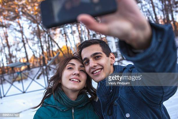 Happy young couple taking selfie through smart phone during winter
